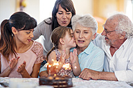 Little girl lwatching sparklers on a birthday cake, sitting on grandmother's lap, with family around - ZEF14254