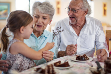 Grandparents celebrating a birthday with their granddaughter, eating chocolate cake - ZEF14263