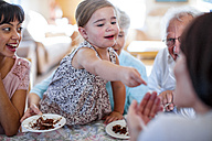 Grandparents celebrating a birthday with their granddaughter, eating chocolate cake - ZEF14266
