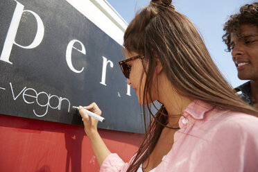 Young woman writing the word 'vegan' on her food truck - SUF00239