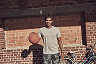 Young man plying baketball in front of brick wall - SUF00245