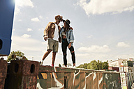 Young couple standing on wall - SUF00251