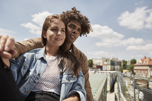 Young couple sitting on a wall - SUF00254