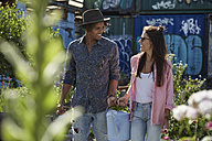 Couple carrying watering can in urban garden - SUF00257