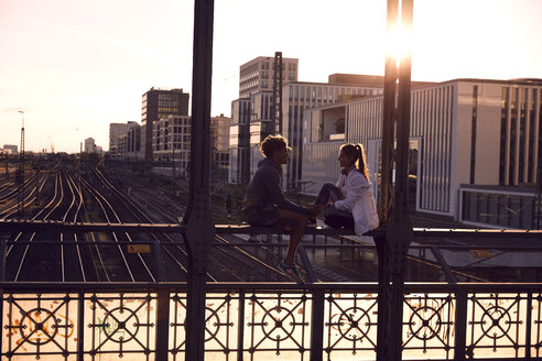 Germany, Munich, Young couple sitting on bridge, enjoying sunset - SUF00263