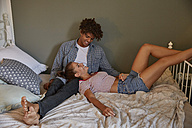 Younh couple sitting on bed, talking - SUF00275