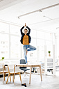 Businesswoman practising yoga on desk in a loft - KNSF02231