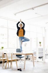 Businesswoman practising yoga on desk in a loft - KNSF02231