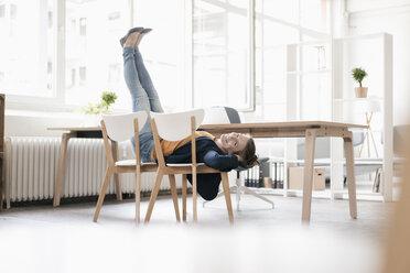 Woman doing gymnastics on chairs in a loft - KNSF02237