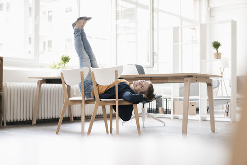 Woman doing gymnastics on chairs in a loft - KNSF02237