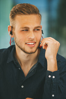 Young man wearing headset outdoors - CHAF01936