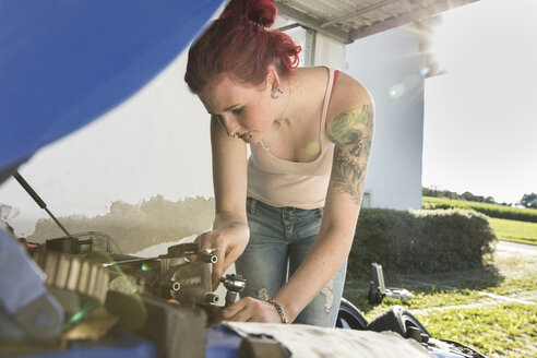 Young woman checking engine - MAEF12386