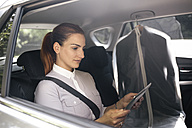 Businesswoman sitting on backseat of a car using tablet - MOMF00187
