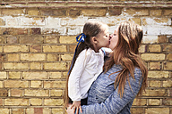 Mother kissing her little daughter in front of brick wall - IGGF00007