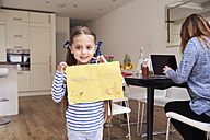 Portrait of smiling little girl showing drawing while her mother working on laptop in the background - IGGF00016