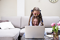 Portrait of smiling mother and little daughter using laptop in the living room - IGGF00019