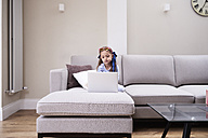 Little girl sitting on the couch looking at laptop - IGGF00022