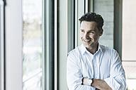 Portrait of confident businessman looking through window - UUF11206