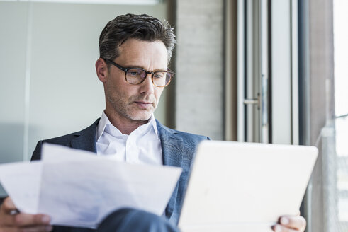 Portrait of serious businessman with documents looking at tablet - UUF11224