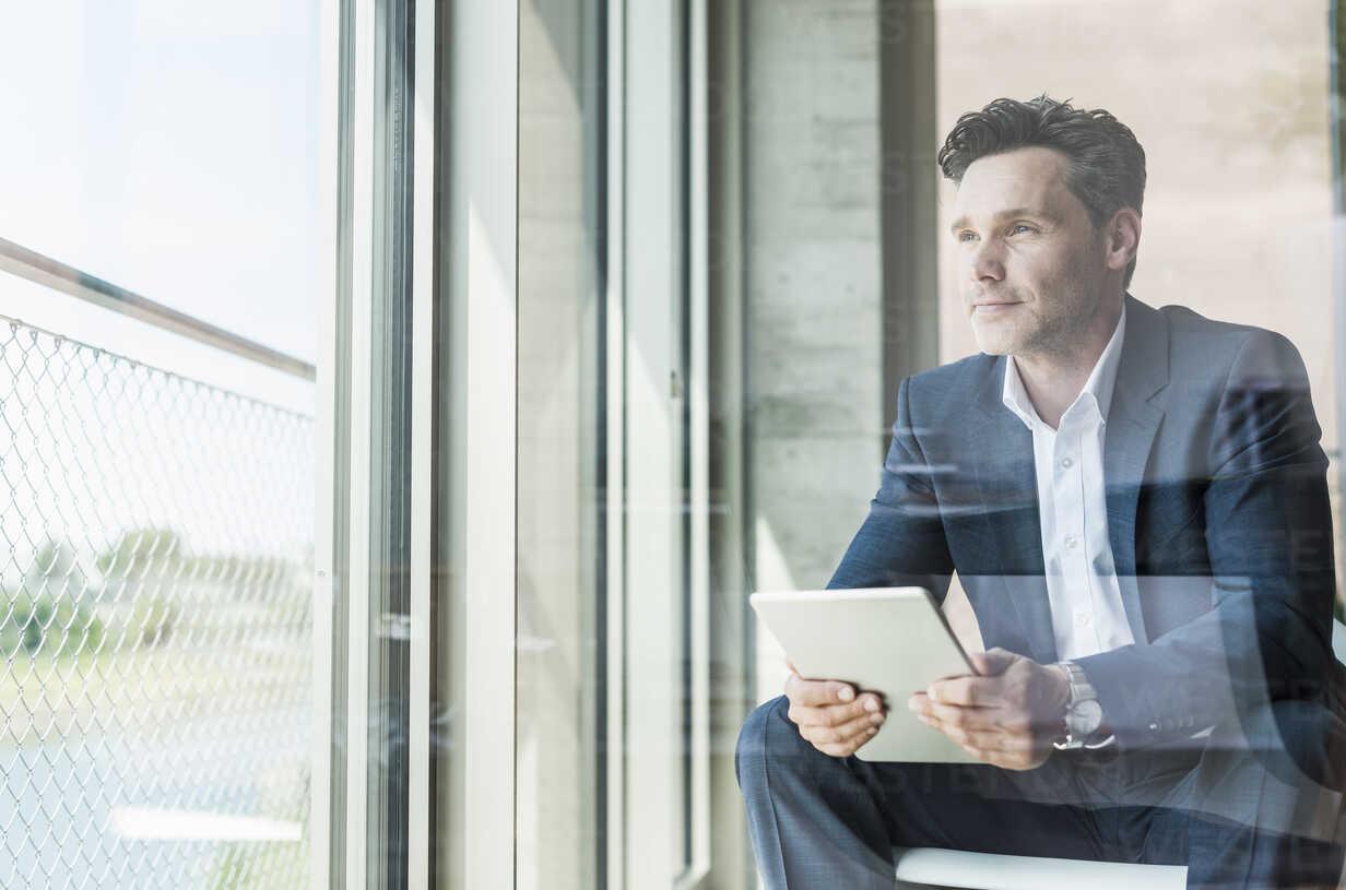 Portrait of businessman with tablet looking through window - UUF11236 - Uwe Umstätter/Westend61