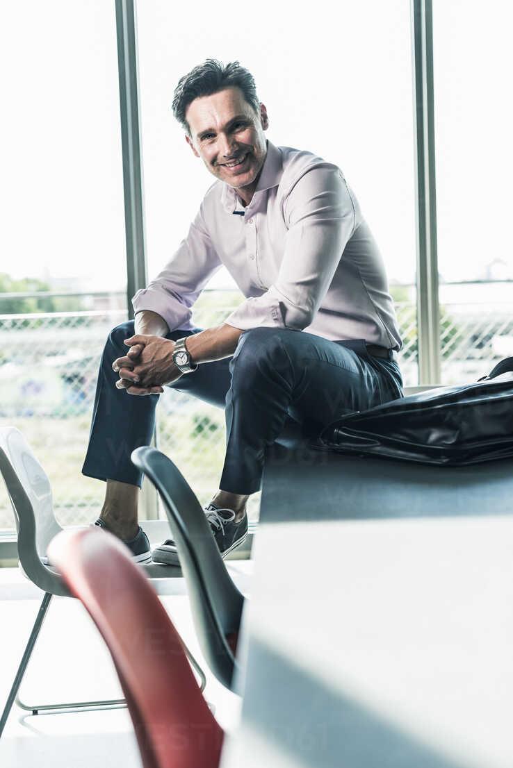 Businessman in office sitting on desk, smiling - UUF11260 - Uwe Umstätter/Westend61