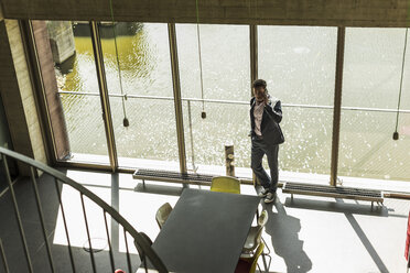 businessman standing by window, making a phone call - UUF11266