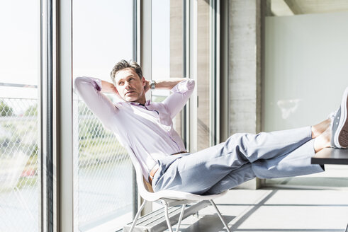 Businessman sitting at desk with feet up, looking out of window - UUF11281