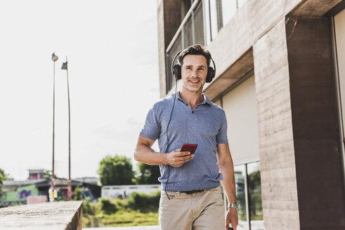 Businessman walking in the city, using smartphone and headphones - UUF11287