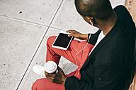 Man sitting in the street, using digital tablet, drinking coffee - JUBF00229