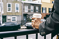 Hands of a man holding cup of coffee on railing - JUBF00232