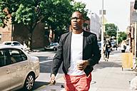 USA, NYC, Brooklyn, Man walking in the street, holding cup of coffee - JUBF00235
