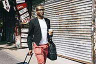 USA, NYC, Brooklyn, Businessman with bags walking in the street - JUBF00238