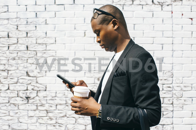 Mid adult man in front of white brick wall, holding smartphone and cup of coffee - JUBF00241