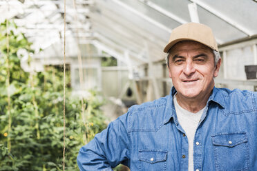 Portrait of smiling senior man in greenhouse - UUF11305