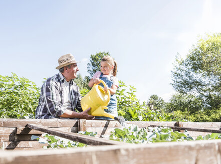 Grandfather and granddaughter in the garden watering plants - UUF11314