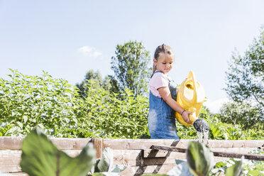 Girl in the garden watering plants - UUF11317