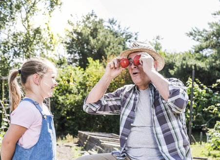 Playful grandfather with granddaughter in the garden - UUF11320