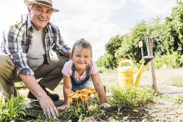 Portrait of happy grandfather and granddaughter in the garden - UUF11335