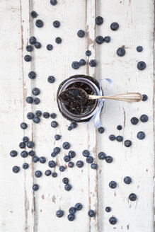 Glass of blueberry jam and blueberries on white wood - LVF06249