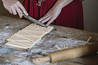 Close-up of woman preparing dough for croissants - ALBF00140