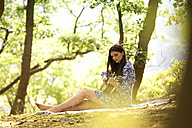 Young woman playing guitar in forest - MFRF00935