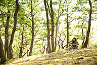 Young woman playing guitar in forest - MFRF00938