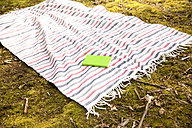 Book lying on blanket in forest - MFRF00941