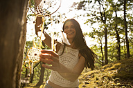 Happy woman hanging dream catcher on a tree - MFRF00944