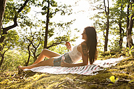 Smiling young woman in forest lying on blanket with drink and apple - MFRF00947