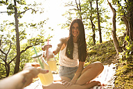 Smiling young woman in forest sitting on blanket clinking drinking bottle - MFRF00950