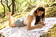 Young woman lying on blanket in forest writing a letter - MFRF00953