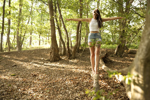 Young woman in forest balancing on a log - MFRF00956