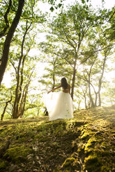 Rear view of young woman in forest wearing tulle skirt - MFRF00959