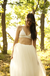 Young woman in forest wearing tulle skirt and bra - MFRF00962